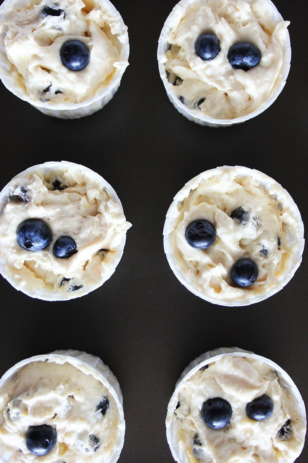 Muffin cups filled with blueberry muffin batter, topped with extra fresh blueberries