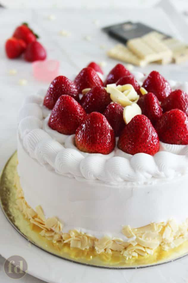 A Japanese strawberry shortcake frosted with Chantilly cream and topped with fresh whole strawberries