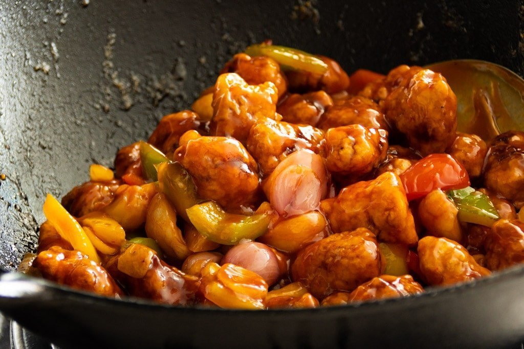 Tossing crispy sweet and sour pork in sweet and sour sauce in a wok