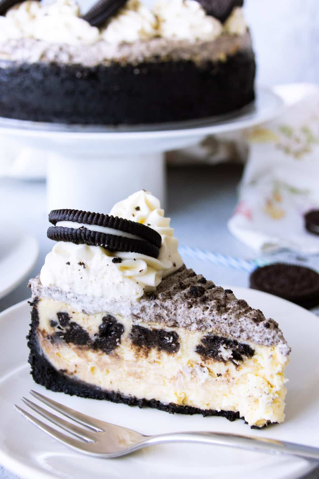 A slice of Oreo cheesecake, topped with Oreo whipped cream and vanilla swirl, and Oreo cookie