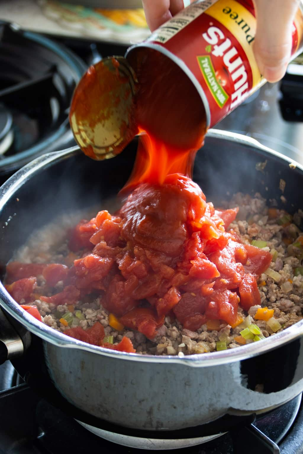 Adding diced tomatoes, tomato sauce and paste to a cooking pot of bolognese sauce
