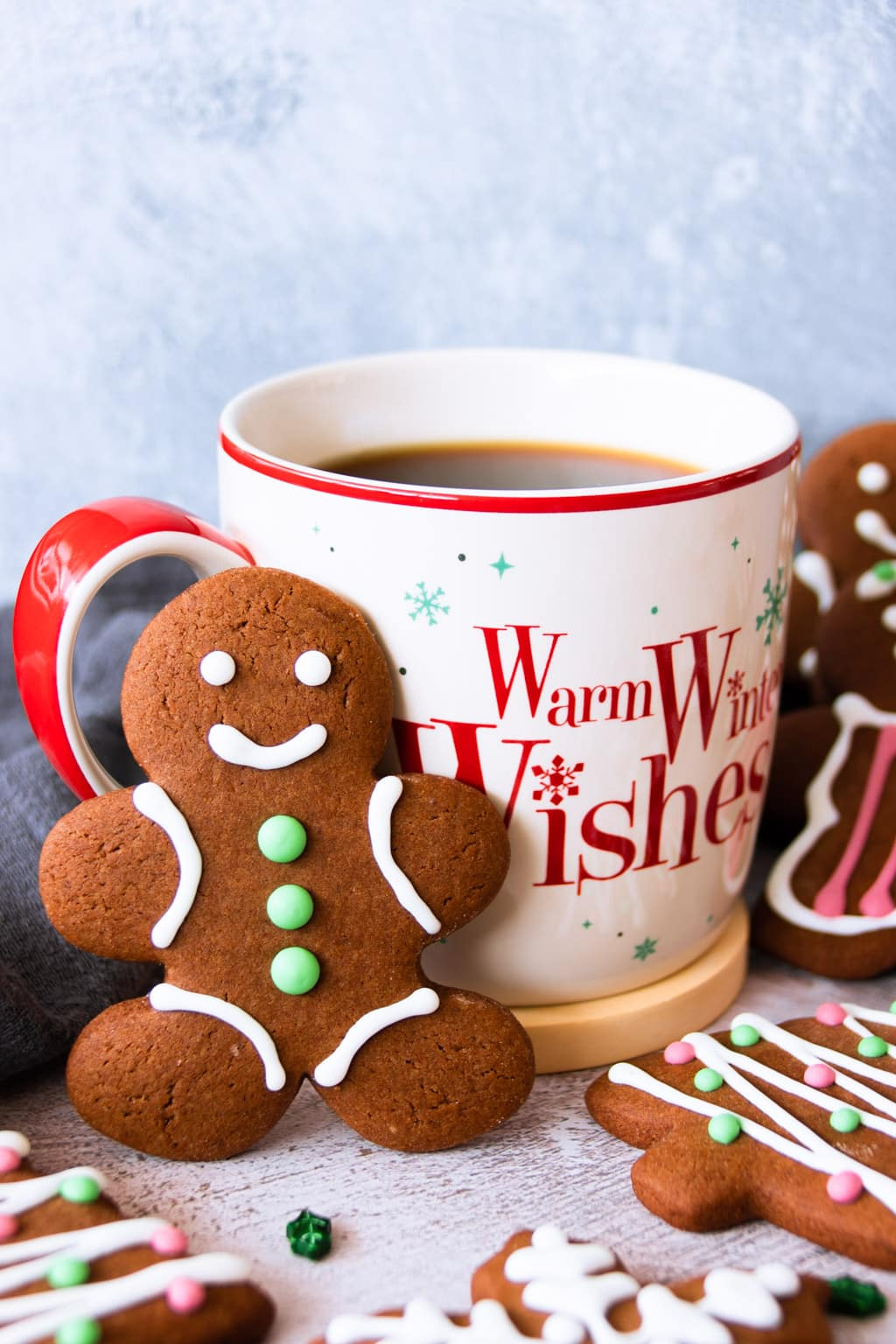 A gingerbread man cookie with a cup of hot coffee
