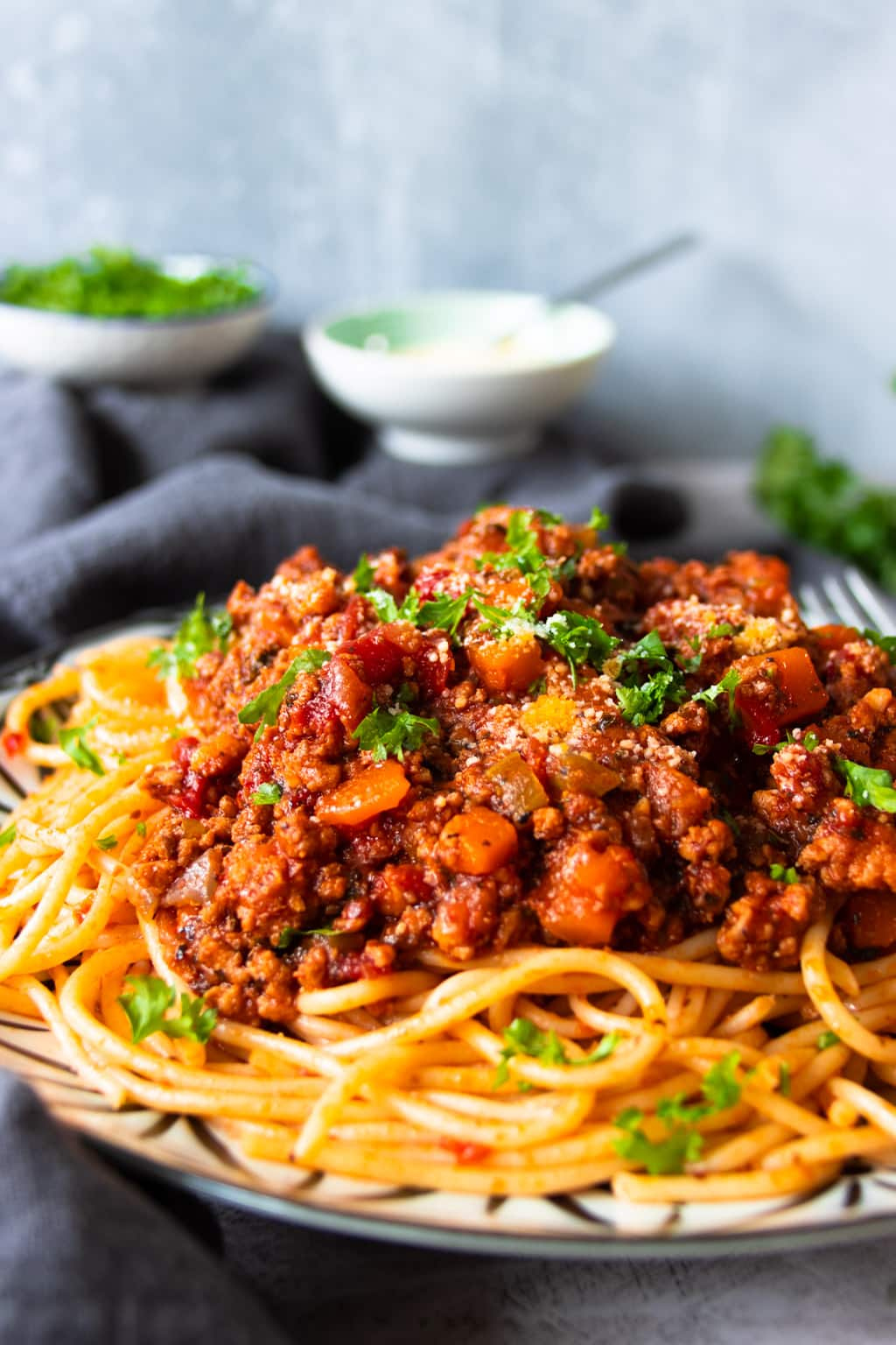 Spaghetti Bolognese served on a plate, garnished with chopped parsley and grated  Parmesan cheese