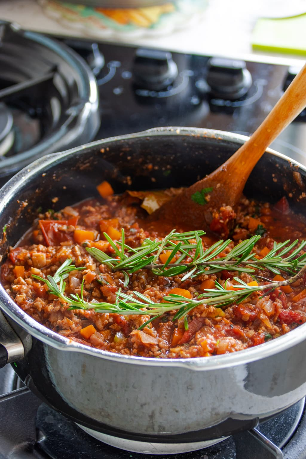Stewing bolognese sauce in a pot, with added rosemary herbs
