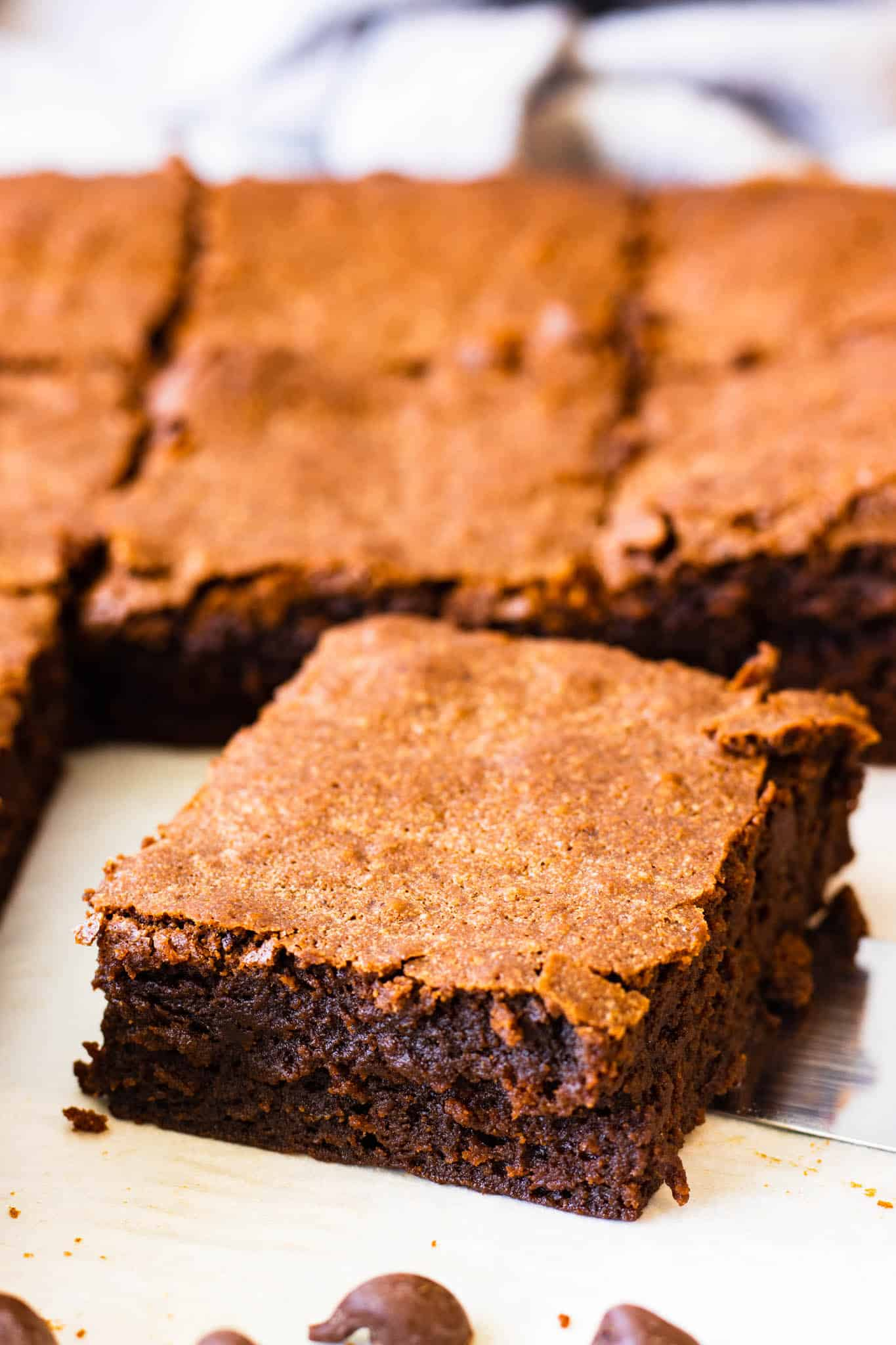 Moist and fudgy brownie slice with paper thin top crust