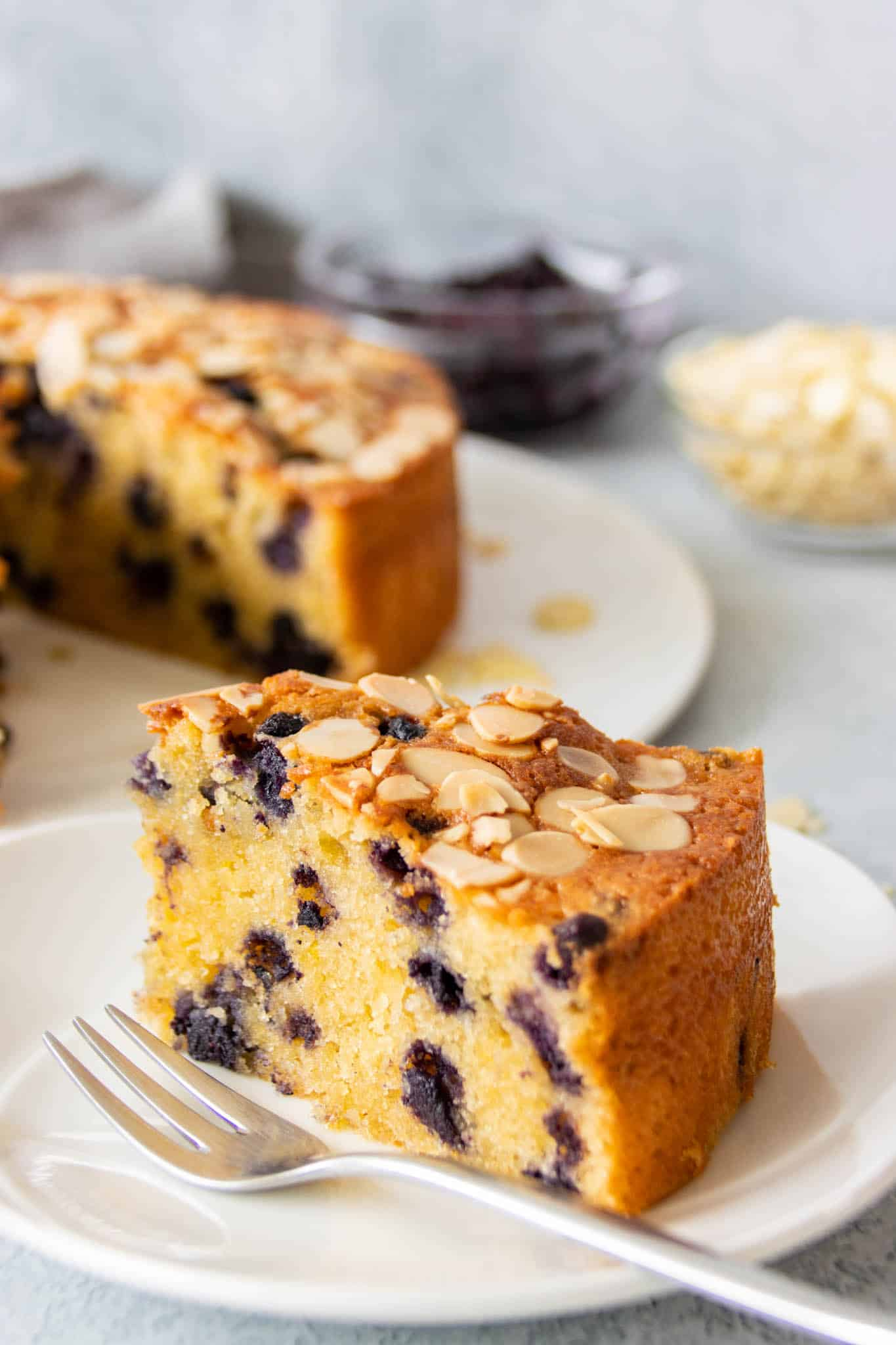 A slice of coconut, almond and blueberry cake, served on a plate