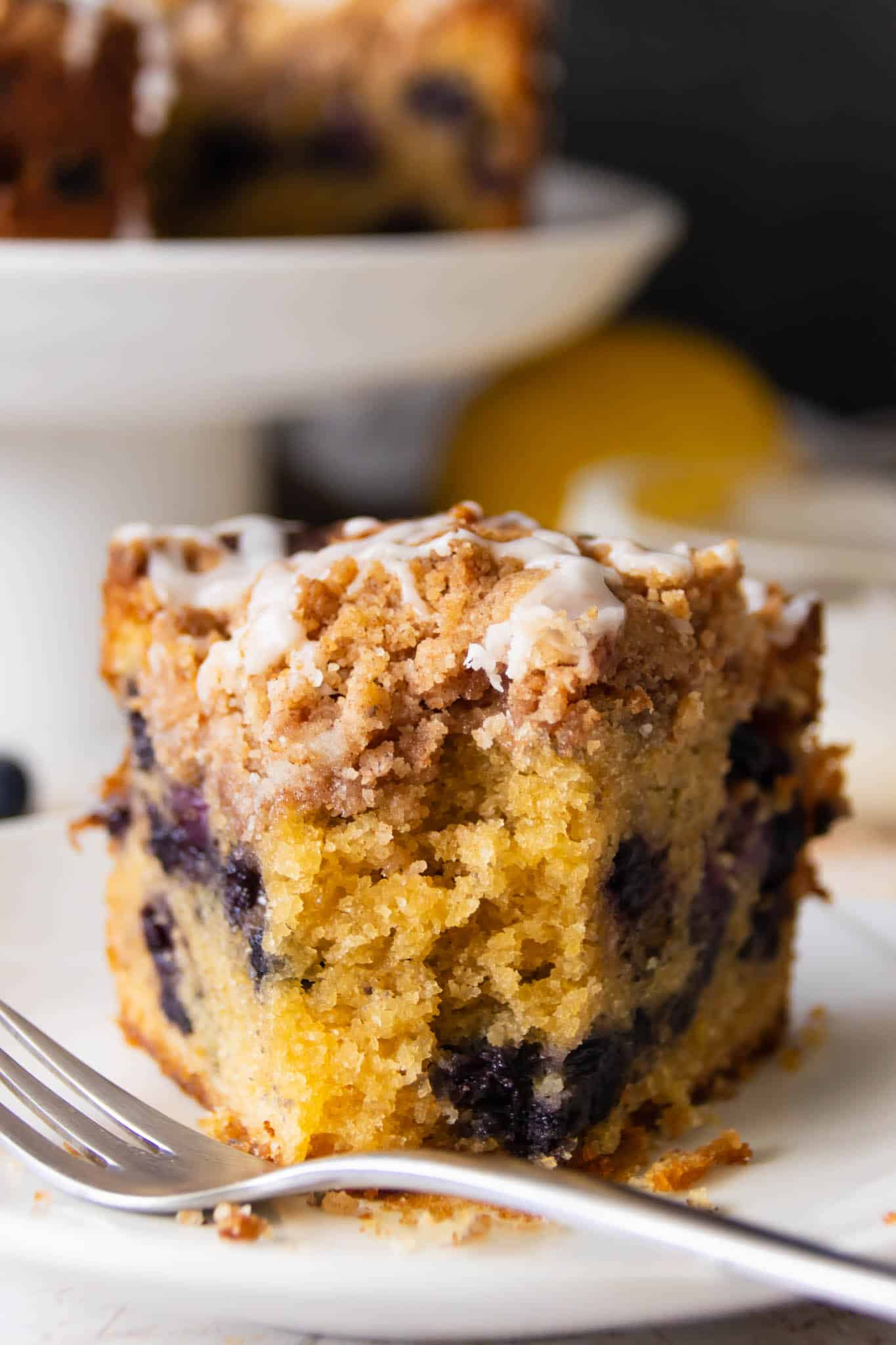 The moist and tender crumb of a blueberry crumble cake slice, drizzled with lemon glaze