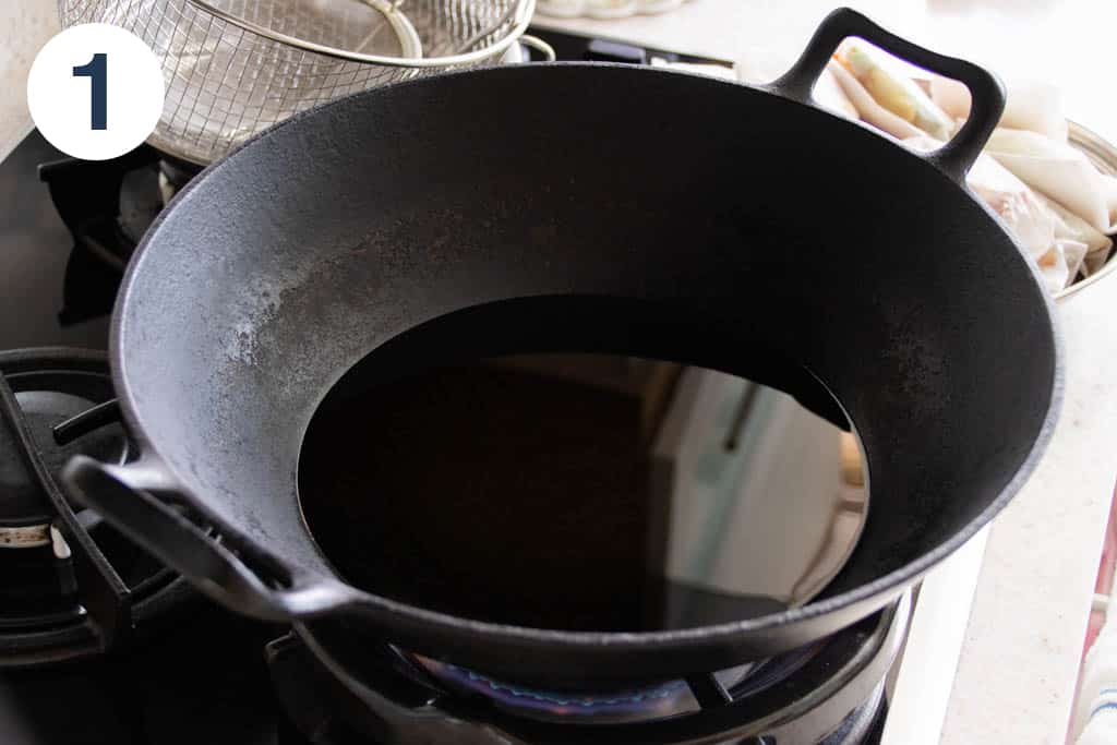 A wok filled with oil to fry paper-wrapped chicken