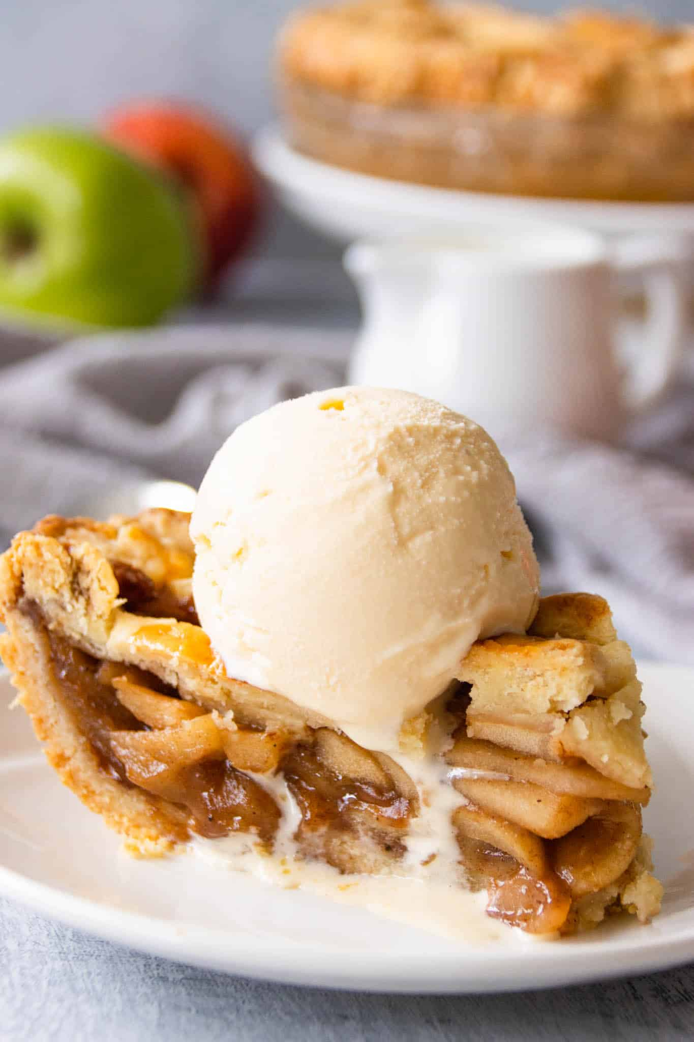 A warm slice of homemade apple pie served with a scoop of vanilla ice cream