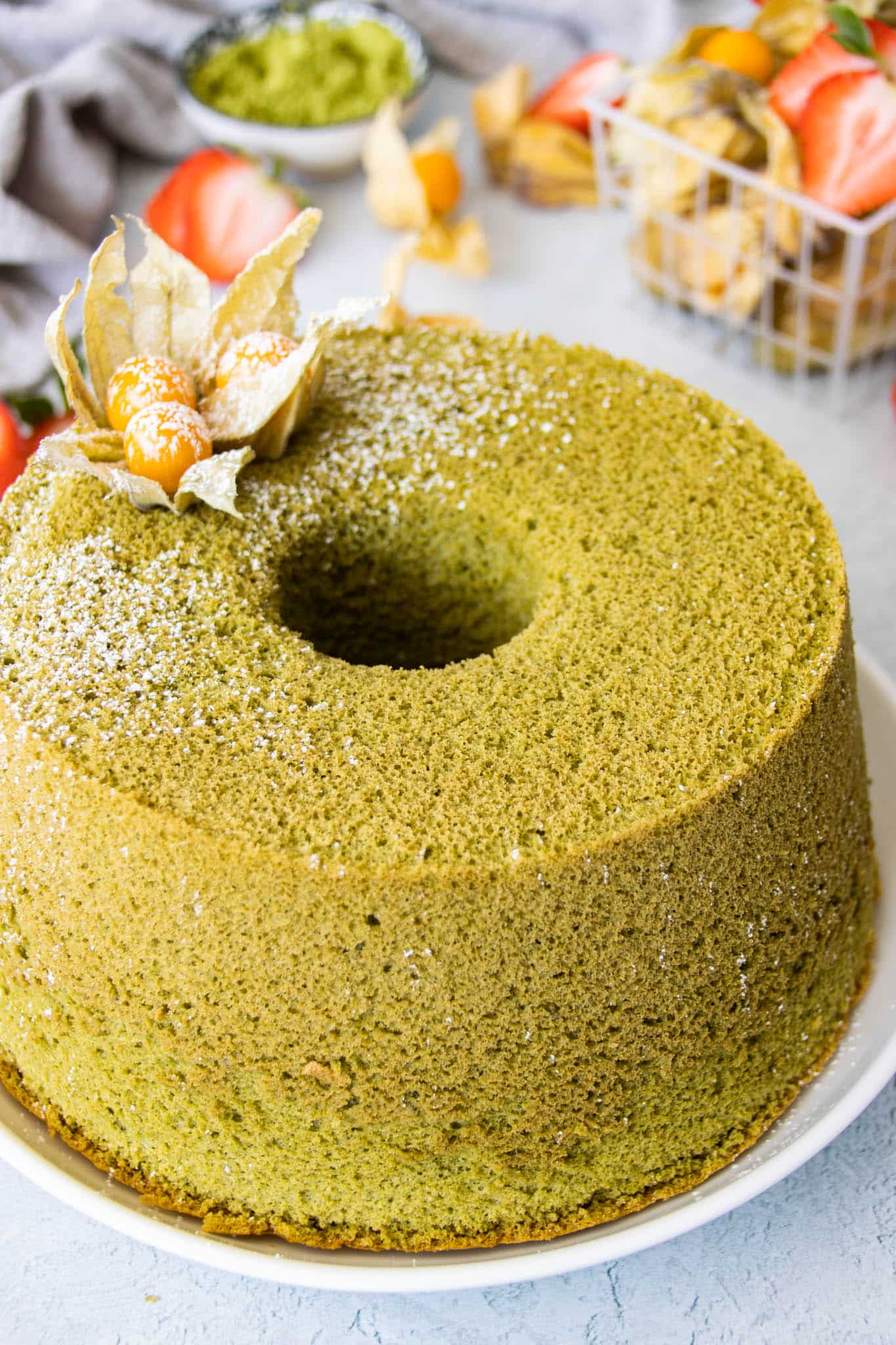Matcha (green tea) chiffon cake with a light dusting of confectioner's sugar and golden berries