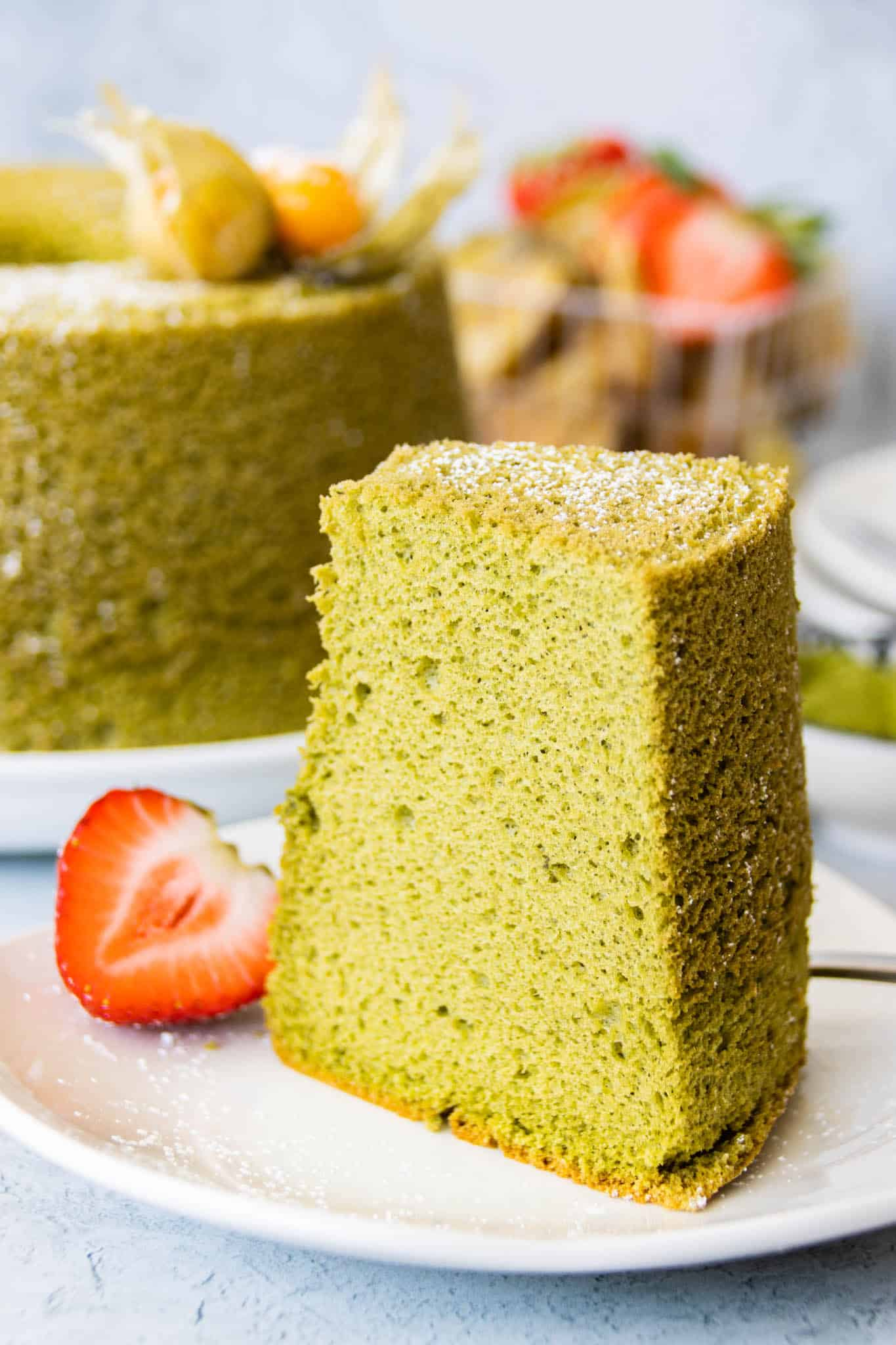 A slice of matcha (green tea) chiffon cake with a light dusting of confectioner's sugar and strawberry slice on a plate