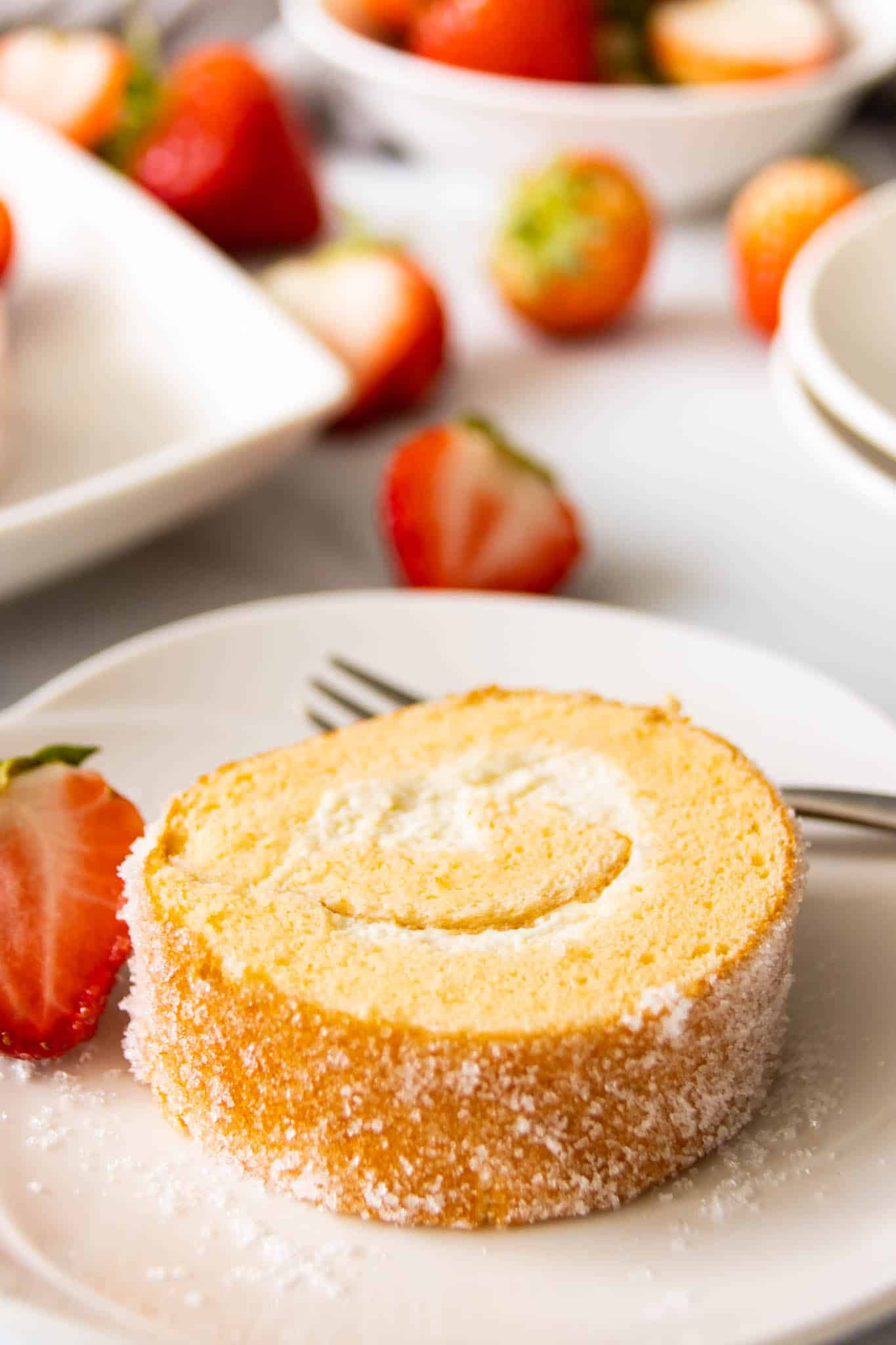 Sugar Swiss roll, served on a plate with fresh strawberries