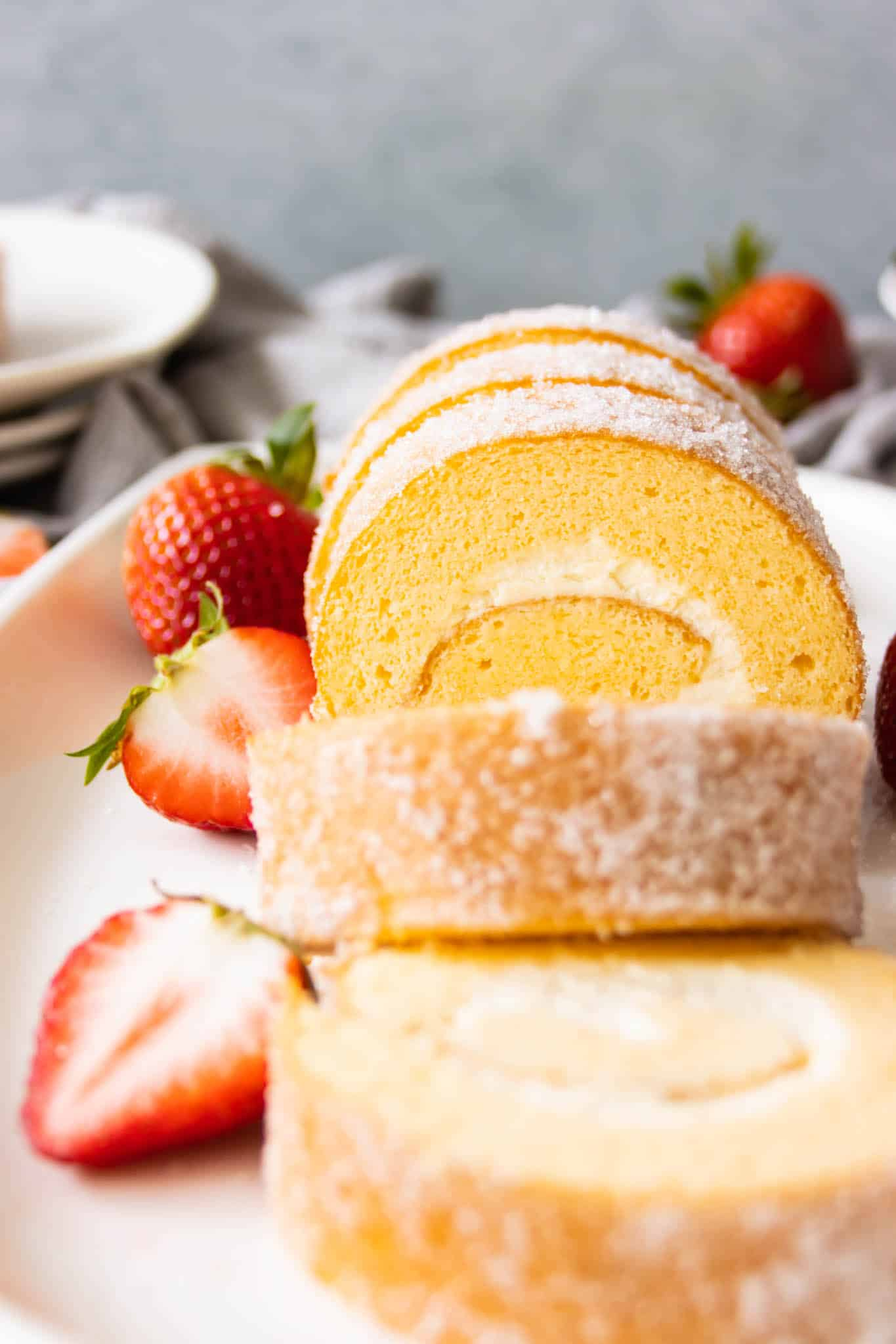 Sugar-coated vanilla Swiss roll cake filled with Chantilly cream, and served with fresh strawberries.