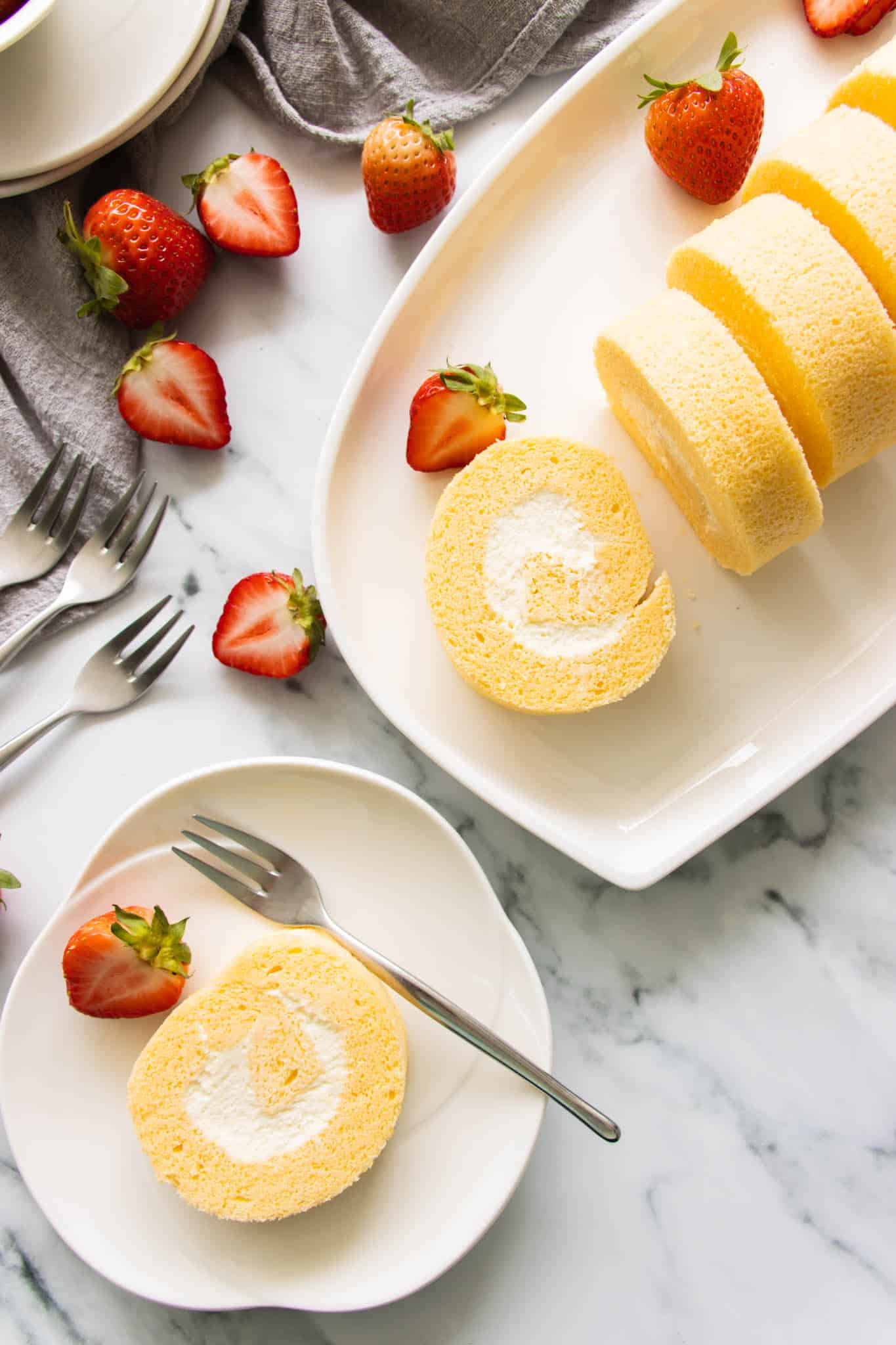 Vanilla swiss rolls on a serving plate with fresh strawberries