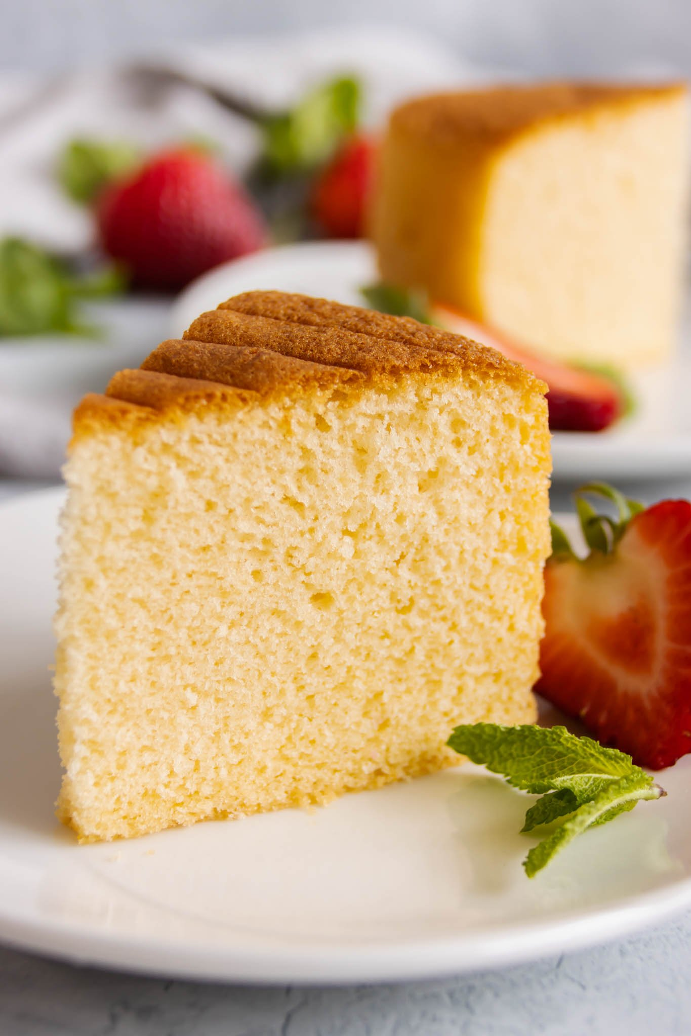 A slice of vanilla sponge cake, served with fresh-cut strawberry and garnished with mint leaves