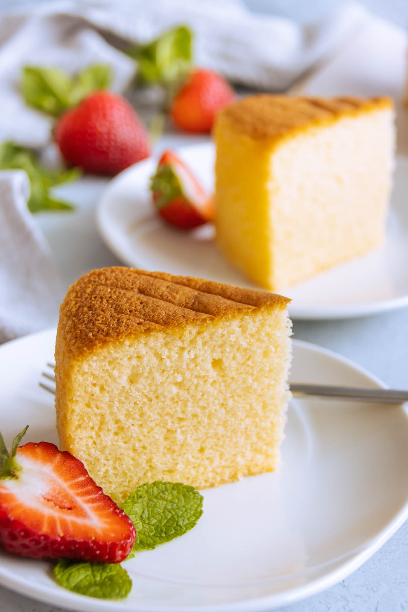 Vanilla genoise sponge cake slice served on a plate with fresh cut fruit